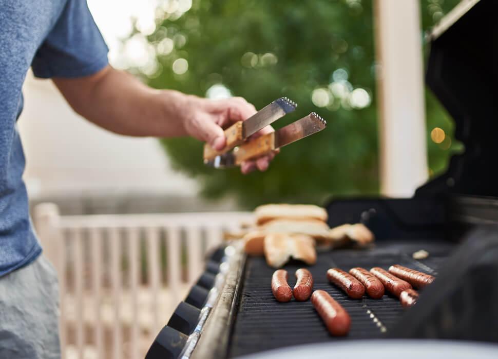 man bbqing hot dogs